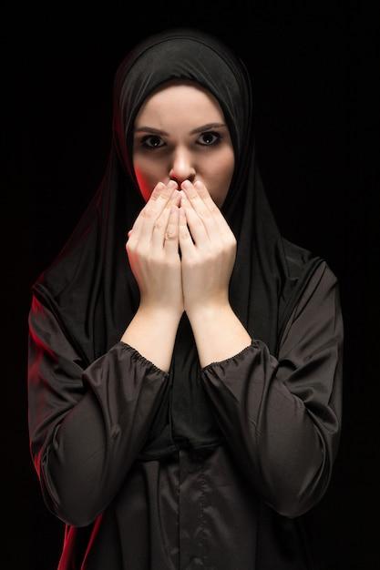 Portret Piękna Poważna Młoda Muzułmańska Kobieta Jest Ubranym Czarnego Hijab Z Rękami Blisko Ona Twarz Jako Modlenia Pojęcia Czerń Premium Zdjęcia