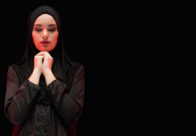 Portret Piękna Poważna Młoda Muzułmańska Kobieta Jest Ubranym Czarnego Hijab Z Zamkniętymi Oczami Jako Modlenia Pojęcie Z Copyspace Premium Zdjęcia