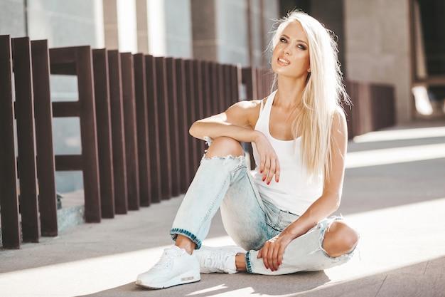 Portret Piękna śliczna Blond Dziewczyna W Białej Koszulce I Cajgach Pozuje Outdoors. śliczny Dziewczyny Obsiadanie Na Asfalcie Na Ulicie Darmowe Zdjęcia