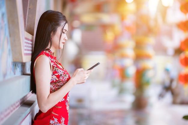 Portret Piękna Uśmiecha Się Azjatycka Młoda Kobieta Ubrana W Czerwony Tradycyjny Chiński Cheongsam I Pisze Wiadomość Na Smartfonie Z Okazji Chińskiego Festiwalu Noworocznego W Chińskiej świątyni Premium Zdjęcia