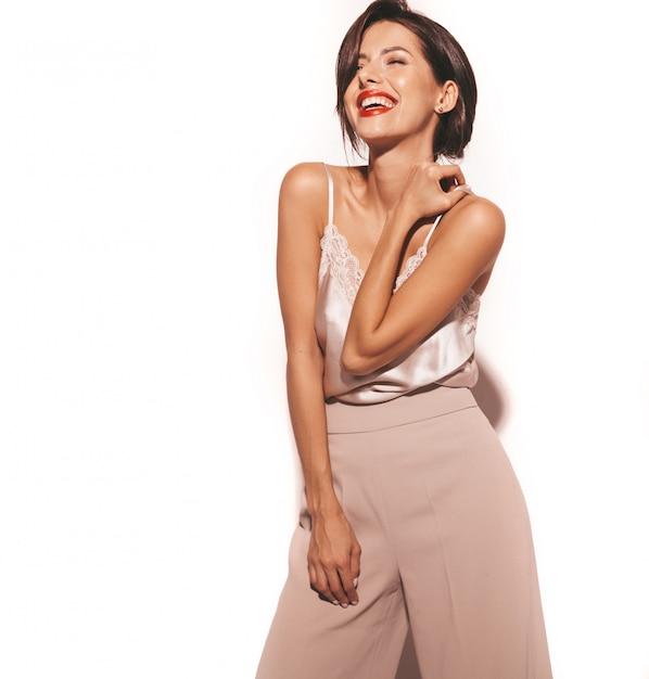 Portret Piękna Uśmiechnięta Zmysłowa Brunetki Kobieta. Dziewczyna W Eleganckich Beżowych Klasycznych Ubraniach I Szerokich Spodniach. Model Na Białym Tle Darmowe Zdjęcia