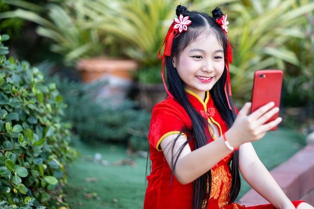 Portret Piękne Uśmiechy Cute Little Asian Dziewczyna Ubrana W Czerwony Tradycyjny Chiński Cheongsam, Biorąc Selfie Ze Smartfonem Premium Zdjęcia