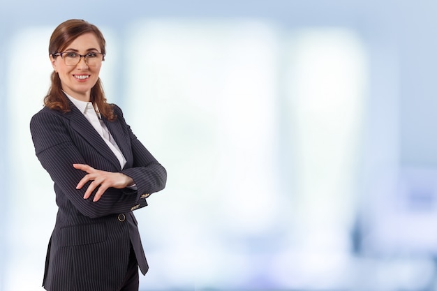 Portret Pięknego Bizneswomanu 50 Uszu Starych W Skrzyżowanych Ramionach Pozuje W Biurze. Premium Zdjęcia