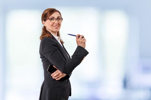 Portret Pięknego Bizneswomanu 50 Uszu Starych Z Telefonem Komórkowym I Piórem W Biurze. Premium Zdjęcia