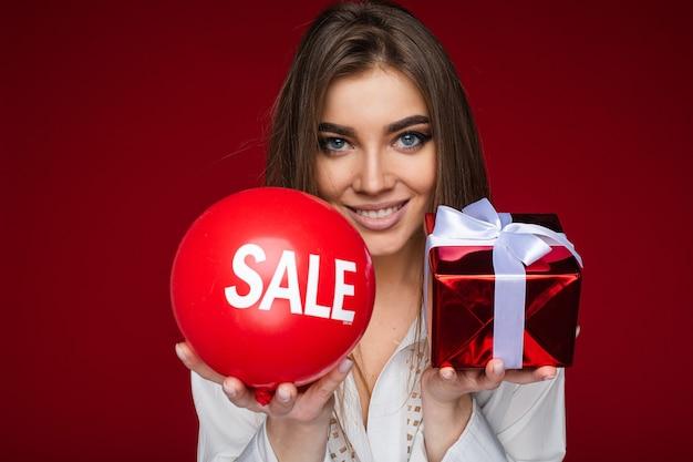 Portret Pięknej Brunetki Kobiety W Białej Koszuli Oferującej Czerwony Balon Z Naklejką Sprzedaży I Zapakowany Czerwony Prezent Z Białym, Aby Ukłonić Się Przed Kamerą. Darmowe Zdjęcia