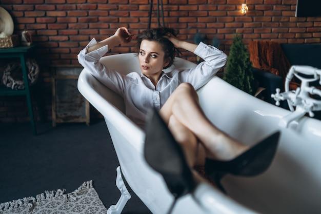 Portret Pięknej Brunetki Leżącej W Pustej łazience, Trzymając Nogi W Górze, Ubrana W Białą Koszulę I Czarne Buty Premium Zdjęcia