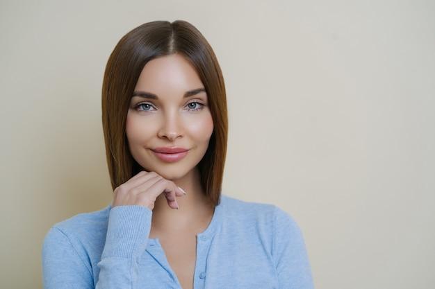 Portret Pięknej Ciemnowłosej Kobiety Ze Zdrową, Naturalną, Czystą Skórą, Dotyka Brody Premium Zdjęcia