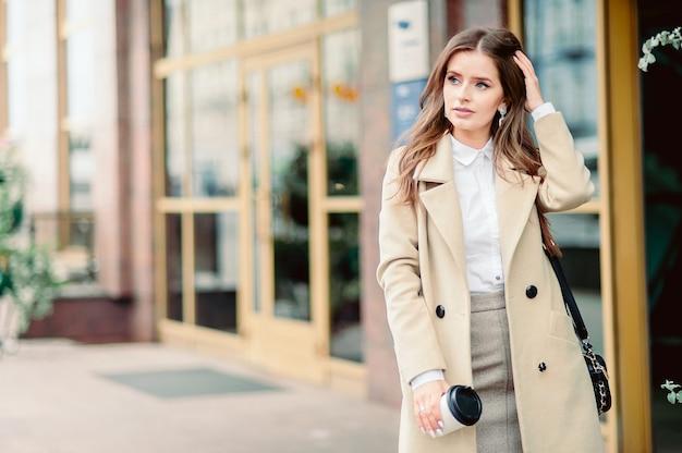 Portret pięknej dziewczyny brunetka spaceru ulicą. trzymając jednorazową zastawę stołową na wynos w jednej ręce. uśmiecha się scena miejska miasta. ciepła, słoneczna jesienna pogoda. na ulicy Premium Zdjęcia