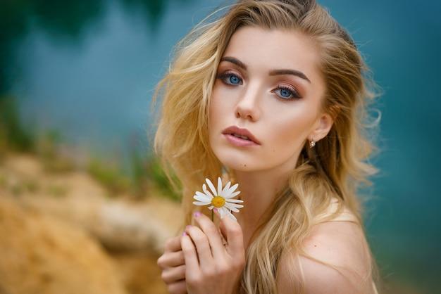 Portret Pięknej Dziewczyny Z Daisy W Dłoniach, Piękny Makijaż Premium Zdjęcia