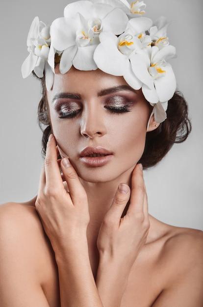 Portret pięknej, efektownej, zmysłowej modelki brunetka z kwiatami Premium Zdjęcia