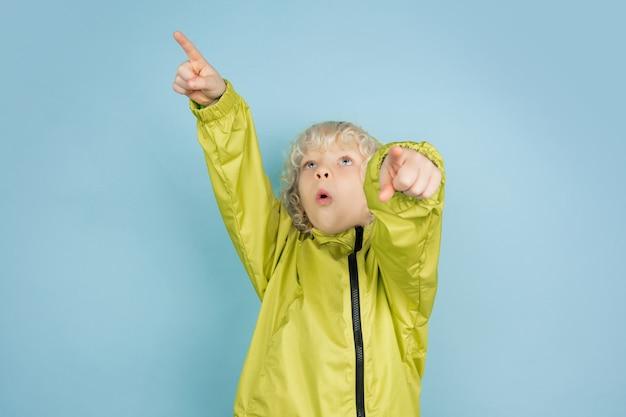Portret Pięknej Kaukaski Chłopczyk Na Białym Tle Na Niebieskim Tle Studio. Blondynka Kręcone Męski Model. Pojęcie Wyrazu Twarzy, Ludzkich Emocji, Dzieciństwa, Reklamy, Sprzedaży. Darmowe Zdjęcia
