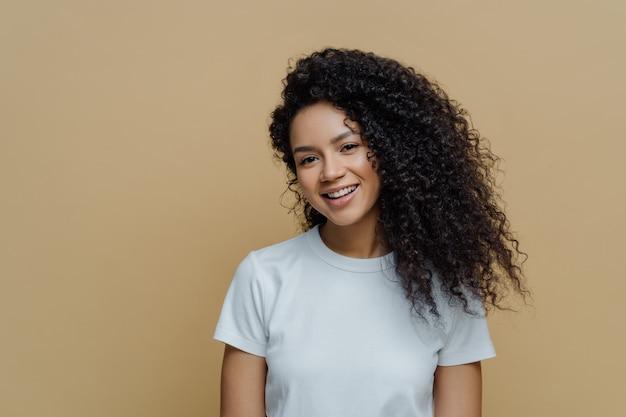 Portret Pięknej Kobiety O Kręconych, Krzaczastych Włosach Delikatnie Się Uśmiecha Premium Zdjęcia