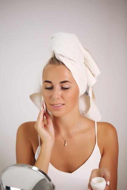 Portret Pięknej Kobiety Stosowania Kremu Do Pielęgnacji Skóry Premium Zdjęcia