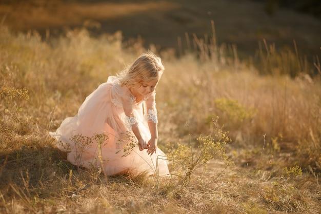 Portret pięknej małej dziewczynki księżniczki w różowej sukience. Premium Zdjęcia