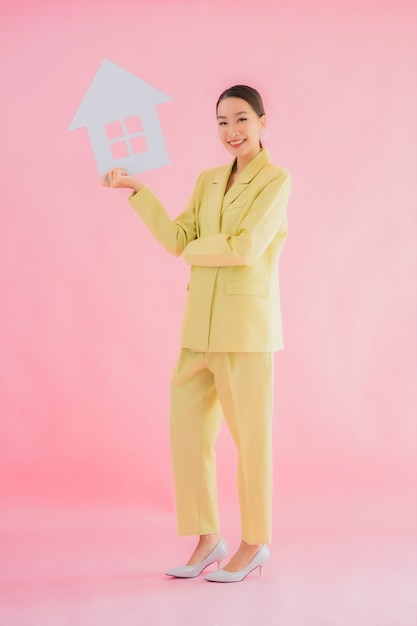 Portret Pięknej Młodej Azjatyckiej Kobiety Biznesu Pokaż Znak Domu Lub Domu Na Kolor Na Białym Tle Darmowe Zdjęcia