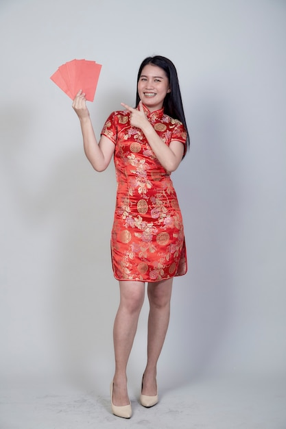 Portret Pięknej Młodej Azjatyckiej Kobiety Ubrana W Chińską Sukienkę Z Czerwonym Pakietem Prezent Pieniężny Gratulacyjny Powitanie Szczęśliwego Nowego Roku 2021 Odizolowany Na Jasnoszarym Tle Z Miejscem Na Kopię Premium Zdjęcia