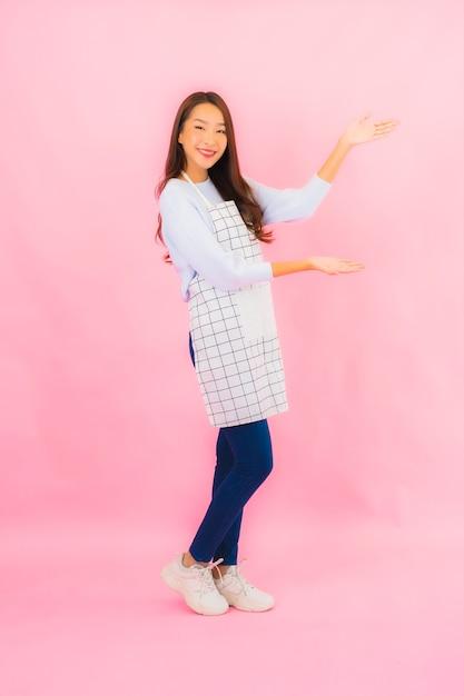 Portret Pięknej Młodej Azjatyckiej Kobiety W Kuchni Nosić Fartuch Na Różowej ścianie Na Białym Tle Darmowe Zdjęcia