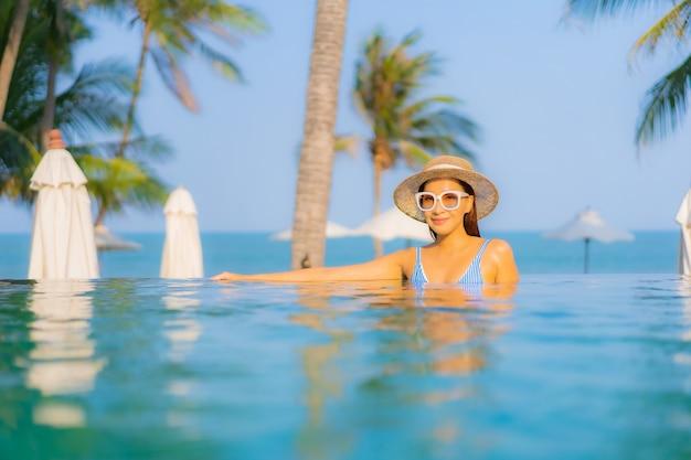 Portret Pięknej Młodej Azjatyckiej Kobiety Zrelaksować Się Uśmiech Cieszyć Się Wypoczynkiem Przy Basenie Prawie Morskiej Plaży Z Widokiem Na Ocean Na Wakacjach Darmowe Zdjęcia