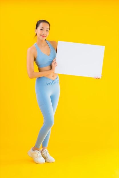 Portret Pięknej Młodej Azjatykciej Kobiety Odzieży Sportwear Przedstawienia Pusty Biały Billboard Na Kolorze żółtym Darmowe Zdjęcia