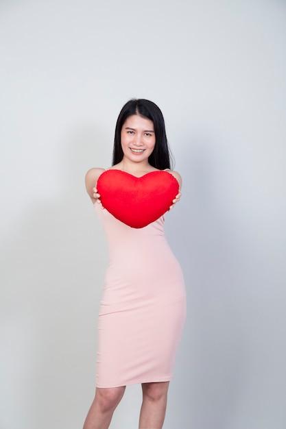 Portret Pięknej Młodej Kobiety Azji W Sukni Pokaż Poduszkę W Kształcie Serca Na Białym Tle Na Jasnoszarym Tle Z Miejsca Na Kopię Premium Zdjęcia