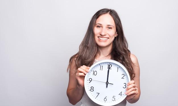 Portret Pięknej Młodej Kobiety, Uśmiechając Się I Trzymając Duży Biały Zegar O Dwunastej Zegar Premium Zdjęcia