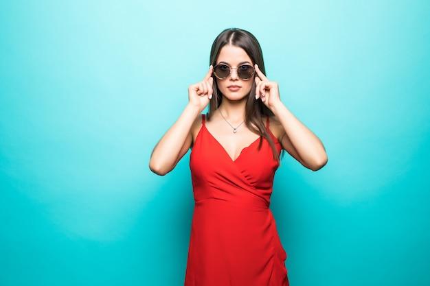 Portret Pięknej Młodej Kobiety W Czerwonej Sukience Na Niebieskiej ścianie Darmowe Zdjęcia