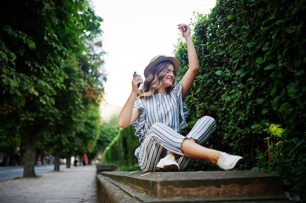 Portret pięknej młodej kobiety w kombinezonie w paski, siedzącej w parku i słuchającej muzyki w słuchawkach. Premium Zdjęcia