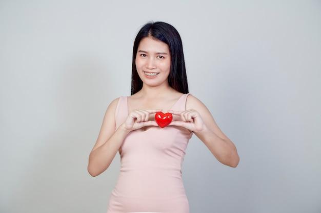 Portret Pięknej Młodej Kobiety Z Azji, Wskazując Kształt Czerwone Serce Na Białym Tle Na Jasnoszarym Tle Z Miejsca Kopiowania Premium Zdjęcia