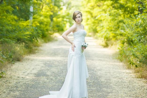 Portret Pięknej Młodej W Przyrodzie. Młoda Kobieta Trzyma Mały Bukiet Białych Róż W Jej Ręce Premium Zdjęcia