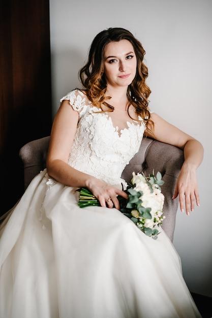 Portret Pięknej Młodej W Sukni Z Bukietem ślubnym Kwiatów Na Fotelu W Stylu Retro. Czułe, Szczęśliwe Emocje Na Twarzy. Premium Zdjęcia