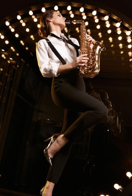 Portret Pięknej Modelki Brunetka W Modnym Garniturze Z Saksofonem, Grając W Restauracji Darmowe Zdjęcia