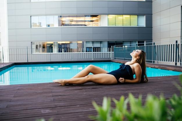 Portret Pięknej Opalonej Sportowej Szczupłej Kobiety Relaks W Basenie Spa. Kreatywny Biały Kapelusz I Bikini. Gorący Letni Dzień I Jasne, Słoneczne światło. Darmowe Zdjęcia
