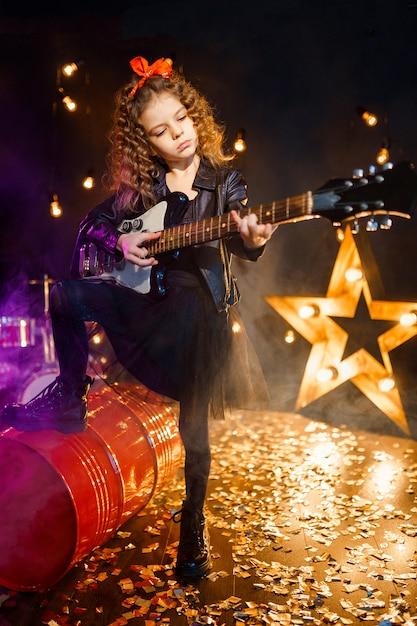 Portret Pięknej Rockowej Dziewczyny Z Kręconymi Włosami W Skórzanej Kurtce I Grającej Na Gitarze Elektrycznej Premium Zdjęcia