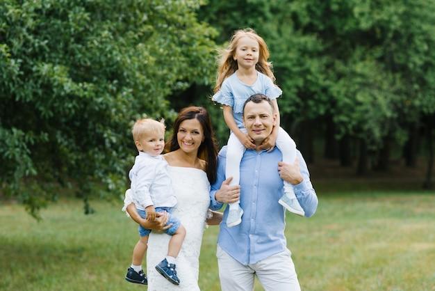 Portret pięknej rodziny: mama, tata, dwuletni syn i pięcioletnia córka. rodzice trzymają dzieci w swoich ramionach. Premium Zdjęcia