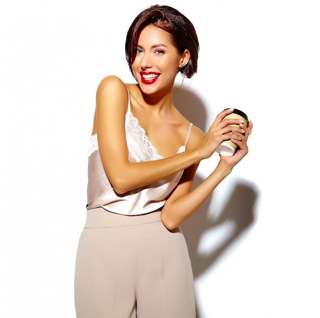 Portret Pięknej Szczęśliwa śliczna Seksowna Brunetki Kobieta Z Czerwonymi Wargami W Szerokich Klasycznych Spodniach Trzyma Plastikową Filiżankę Kawy Na Białym Tle Darmowe Zdjęcia