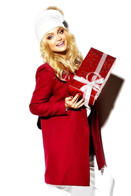 Portret Pięknej Szczęśliwej Słodkiej Uśmiechniętej Blondynki Kobiety Dziewczyny Mienia W Jej Rękach Duży Bożenarodzeniowego Prezenta Pudełko W Przypadkowej Czerwonej Modniś Zimy Ubraniach Darmowe Zdjęcia