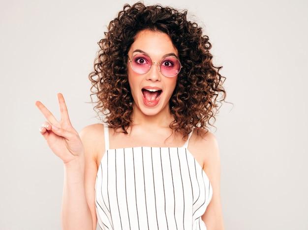 Portret Pięknej Uśmiechający Się Model Z Fryzurą Afro Loki, Ubrany W Letnie Ubrania Hipster. Modna Kobieta śmieszne I Pozytywne Pokazuje Znak Pokoju Darmowe Zdjęcia