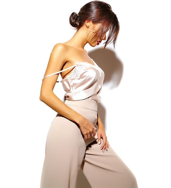 Portret Pięknej Zmysłowej Dziewczyny Brunetka Dama W Eleganckie Białe Klasyczne Ubrania I Szerokie Spodnie Na Białym Tle Darmowe Zdjęcia