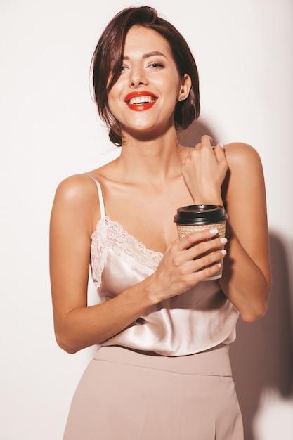 Portret Pięknej Zmysłowej Kobiety Brunetka. Dziewczyna W Eleganckich Beżowych Klasycznych Ubraniach I Szerokich Spodniach. Model Gospodarstwa Plastikowy Kubek Kawy Darmowe Zdjęcia