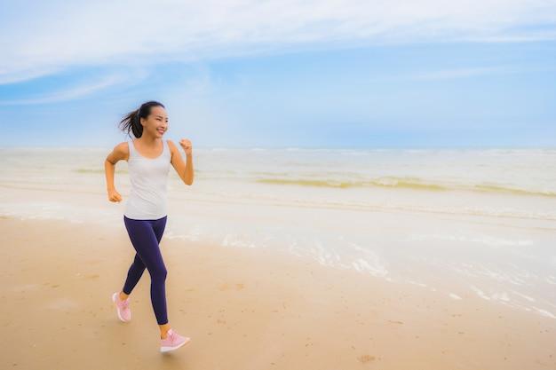 Portret Piękni Potomstwa Bawją Się Azjatykciej Kobiety ćwiczenie Biegać I Jogging Na Plenerowej Natury Morzu I Plaży Darmowe Zdjęcia