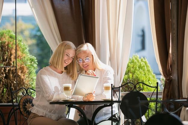 Portret Piękny Dorośleć Matki I Jej Córki Trzyma Filiżankę Siedzi W Domu Darmowe Zdjęcia