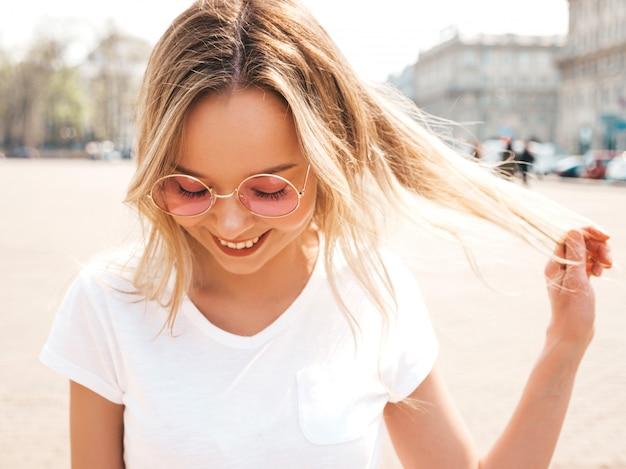 Portret Piękny Uśmiechnięty Blondynu Model Ubierał W Lato Modnisiu Odziewa. Modna Dziewczyna Pozuje Na Ulicy W Okrągłe Okulary Przeciwsłoneczne. śmieszna I Pozytywna Kobieta Ma Zabawę Darmowe Zdjęcia
