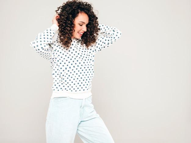 Portret Piękny Uśmiechnięty Model Z Fryzurą Afro Loki Ubrany W Letnie Ubrania Hipster. Seksowna Beztroska Dziewczyna Pozuje W Studio Na Szarym Tle. Modna Kobieta śmieszne I Pozytywne Darmowe Zdjęcia