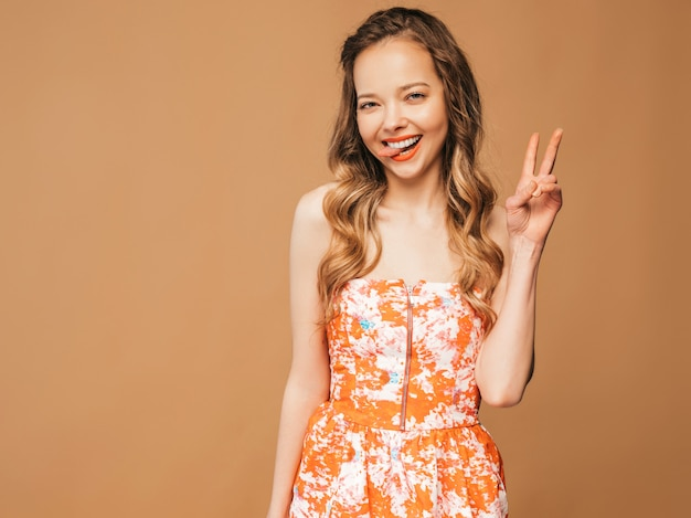 Portret Piękny Uśmiechnięty śliczny Model Z Różowymi Wargami. Dziewczyna W Letniej Kolorowej Sukience. Model Stwarzające. Pokazując Znak Pokoju Darmowe Zdjęcia