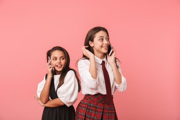 Portret Pięknych Dziewczyn W Mundurkach Szkolnych Za Pomocą Telefonów Komórkowych Do Połączeń, Stojąc Odizolowane Na Czerwonej ścianie Premium Zdjęcia