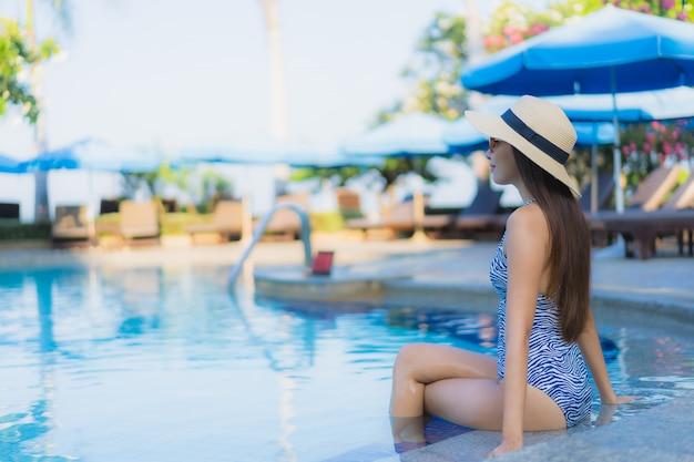 Portret Pięknych Młodych Azjatykcich Kobiet Szczęśliwy Uśmiech Relaksuje Plenerowego Pływackiego Basenu W Kurorcie Darmowe Zdjęcia