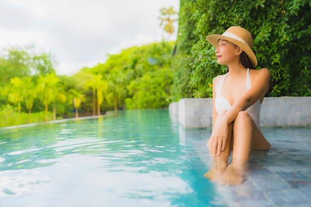 Portret pięknych młodych azjatykcich kobiet szczęśliwy uśmiech relaksuje wokoło plenerowego pływackiego basenu w hotelu Darmowe Zdjęcia