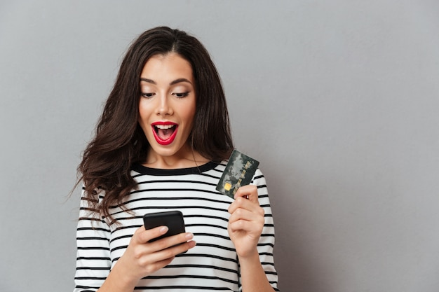 Portret Podekscytowana Dziewczyna Patrząc Na Telefon Komórkowy Darmowe Zdjęcia
