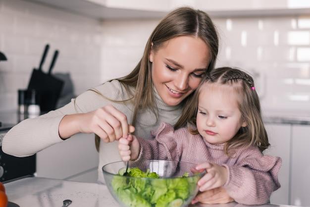 Portret Podekscytowana Kobieta Jedzenie Gotowane Zdrowe Sałatki Z Córką Darmowe Zdjęcia