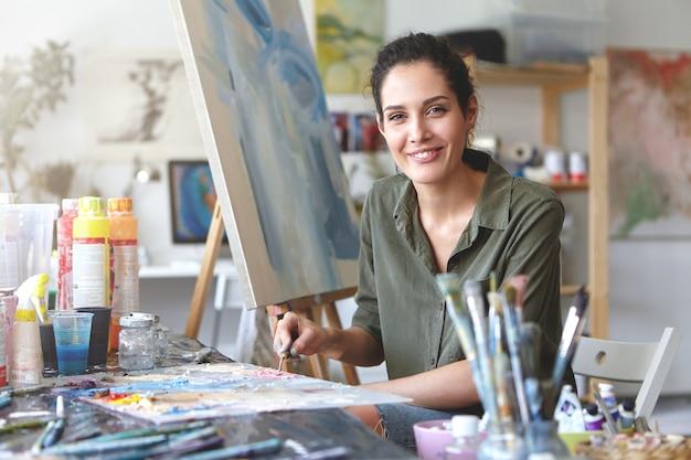 Portret Podekscytowanej Młodej Artystki Brunetki W Swobodnej Bluzce W Kolorze Khaki, Mieszającej Farbę Olejną Na Palecie Za Pomocą Noża Malarskiego, Pasjonatka Swojego Zawodu I Procesu Tworzenia Darmowe Zdjęcia